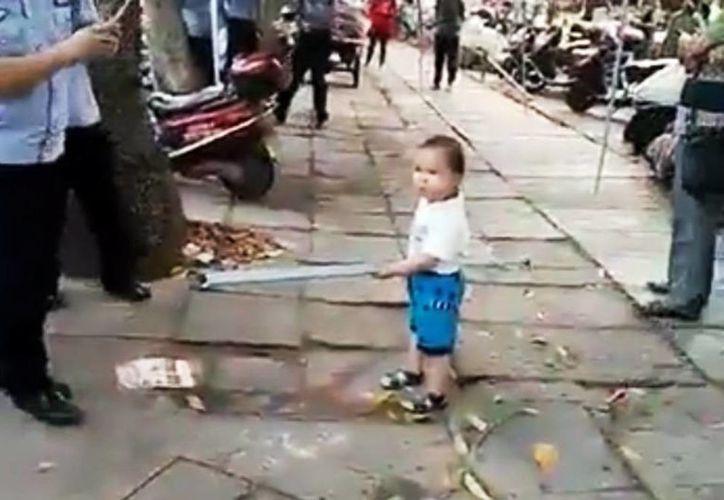 El menor retó a los policias con un tubo más grande que él y gritaba que no toquen a su abuela. (Captura de pantalla/YouTube)