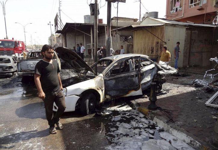 Curiosos iraquíes observan el lugar de un atentado con un coche bomba el pasado 19 de septiembre, en Kirkuk, Irak. (EFE/Archivo)