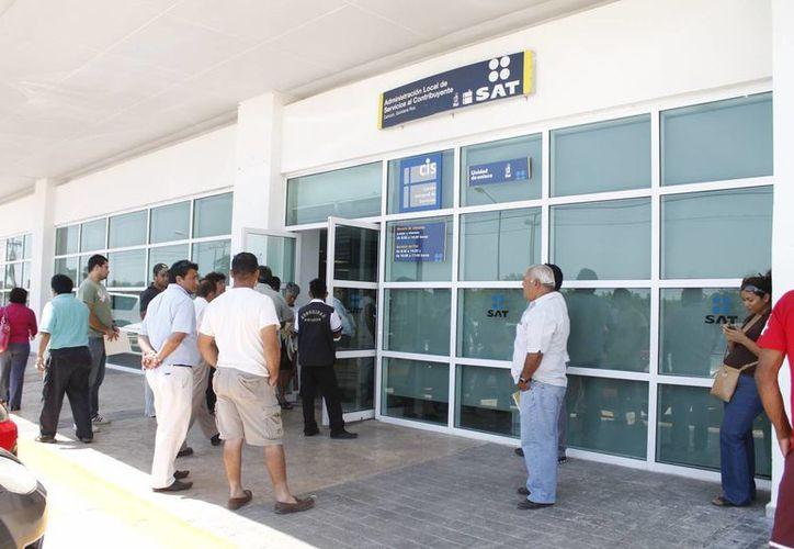 El SAT colocó un stand en el Mercado 28 para apoyar a los contribuyentes que se acerquen y los atienden en las oficinas. (Israel Leal/SIPSE)