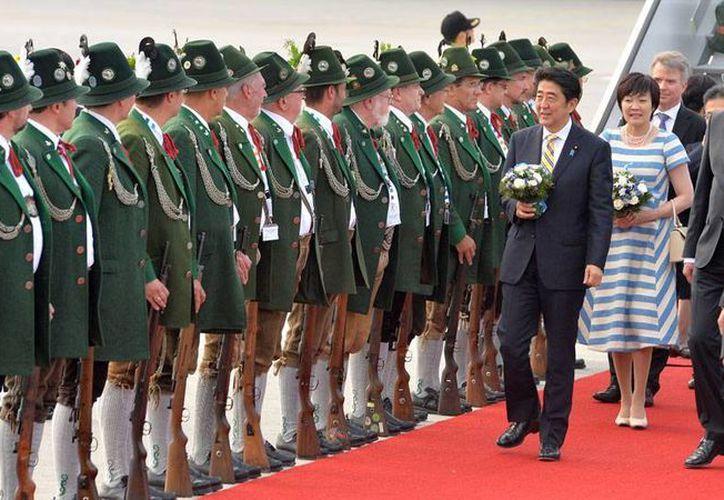 El primer ministro de Japón Shinzo Abe y su esposa Akie Abe llegan a Bavaria, Alemania, para la cumbre del G7, reunión que ha provocado la inconformidad de los ciudadanos que este sábado salieron a las calles para protestar por el encuentro. (AP)