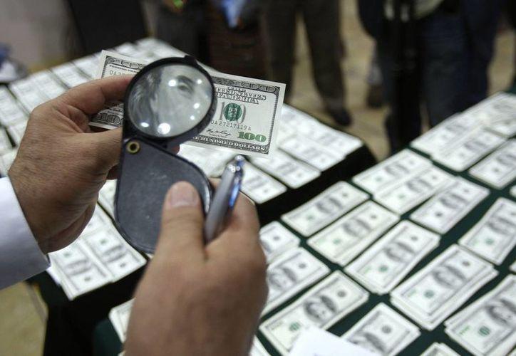 Un detective inspecciona un billete de 100 dólares que se cree es falso. (Agencias)