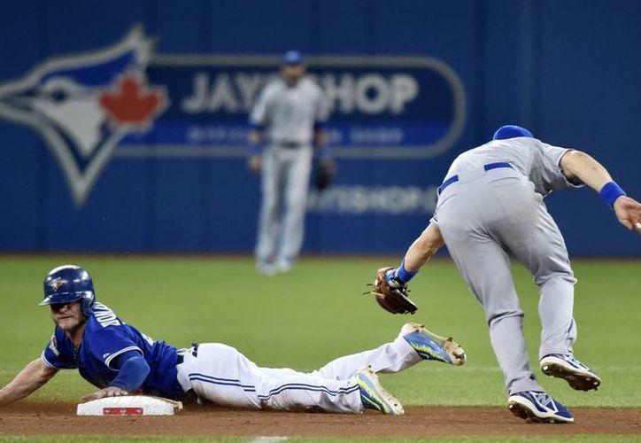Josh Donaldson, de Azulejos (i) se roba la segunda base que cuidaba Ben Zobrist, de Reales, que ganaron y pusieron 3-1 la serie de campeonato de la Liga Americana, rumbo a la Serie Mundial. (AP)