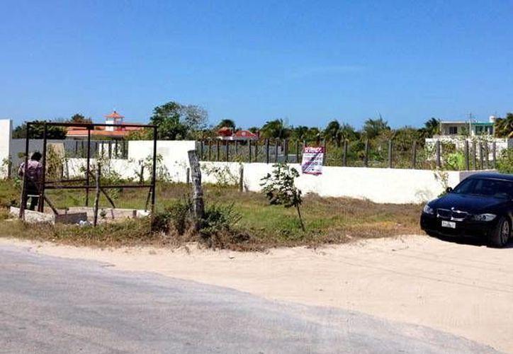 Predios baldíos, sin ninguna estructura, operan como estacionamientos en Chicxulub. (Milenio Novedades)