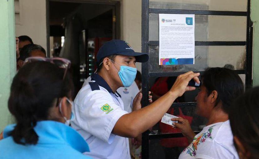 Guardias de seguridad toman la temperatura a los visitantes. (Novedades Yucatán)