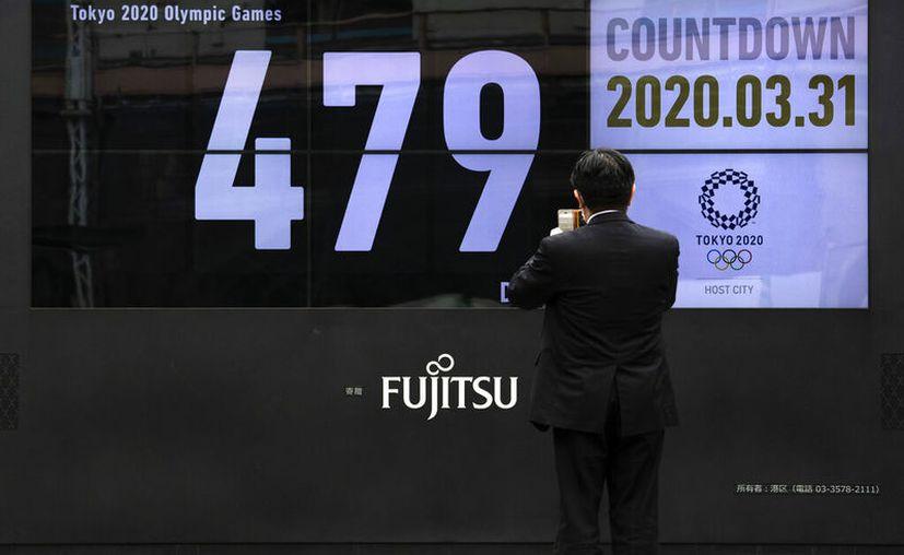 Un hombre capta imagen de la cuenta regresiva para los Juegos Olímpicos en Tokio. (AP Foto/Jae C. Hong)