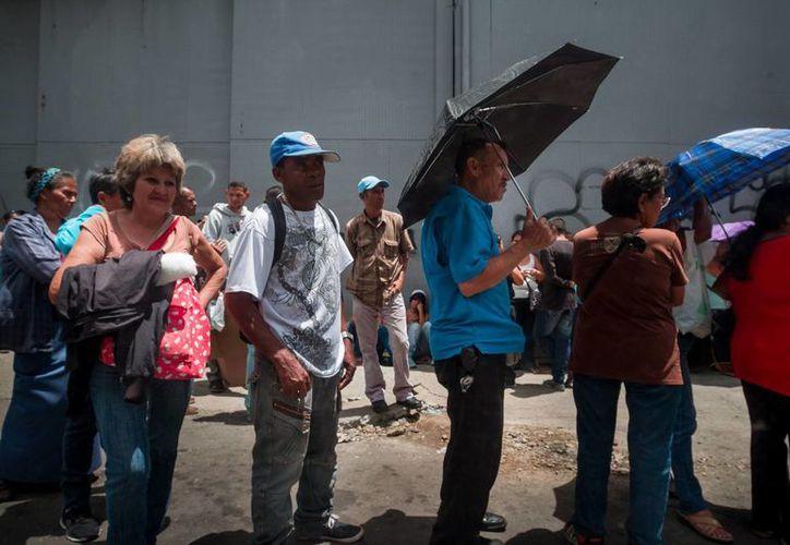 Un grupo de personas hace fila para poder comprar alimentos, en el sector popular Catia, en Caracas, Venezuela. (EFE/Archivo)