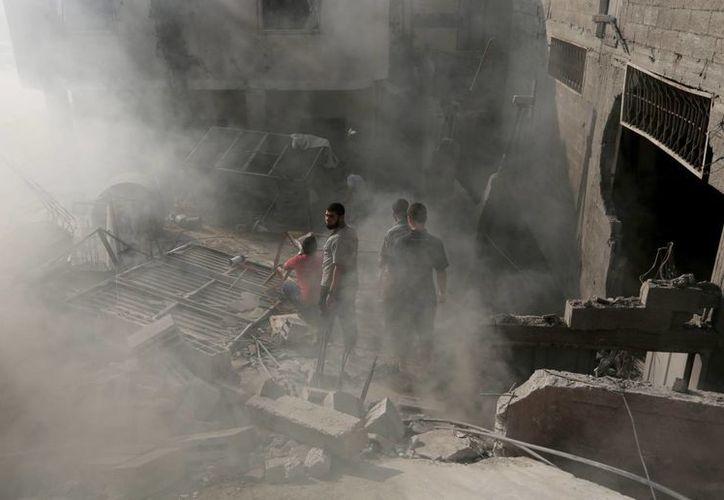 Palestinos inspeccionan los escombros de una casa después de que fue atacada por un misil israelí en Gaza. (Agencias)