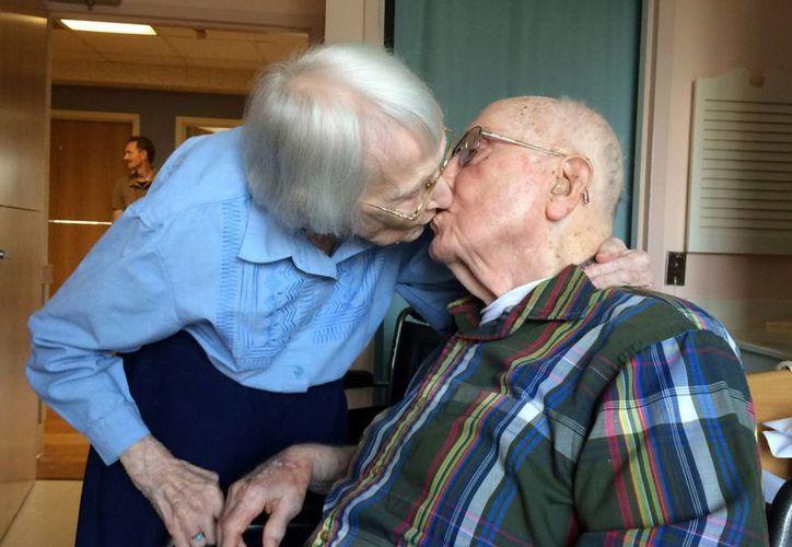 Walter y Leslie Kimmel, ambos de 100 años de edad, se dan un beso en su 75 aniversario de bodas, el martes 18 de agosto de 2015 en la Comunidad de Retiro Charlestown, en Catonsville, Maryland. (Paul J. Kessler/WBFF-TV vía AP)