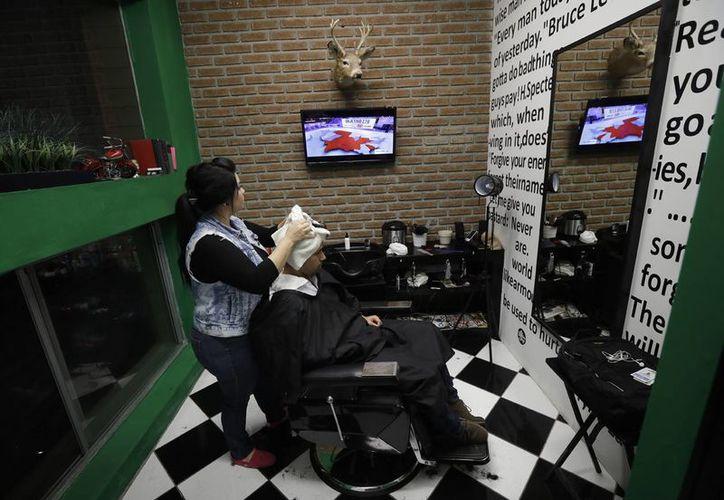 Una peluquera mexicana observa en televisión los resultados de las elecciones estadounidenses, la noche de este martes, en Tijuana. (AP/ Gregory Bull)