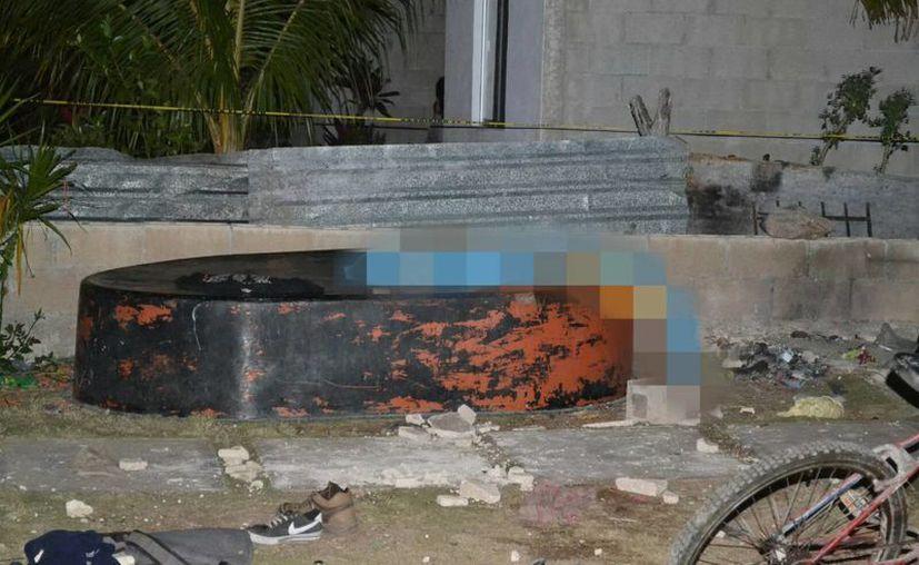 El cadáver del pandillero muerto quedó sobre una estructura de cemento dentro de un predio de la colonia San Antonio Xluch III. (Milenio Novedades)