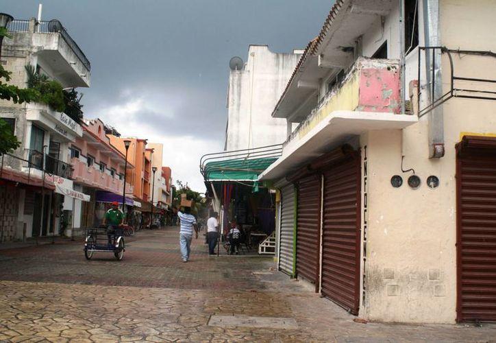 Encargados de negocios se mantuvieron informados durante el paso de la tormenta. (Loana Segovia/SIPSE)