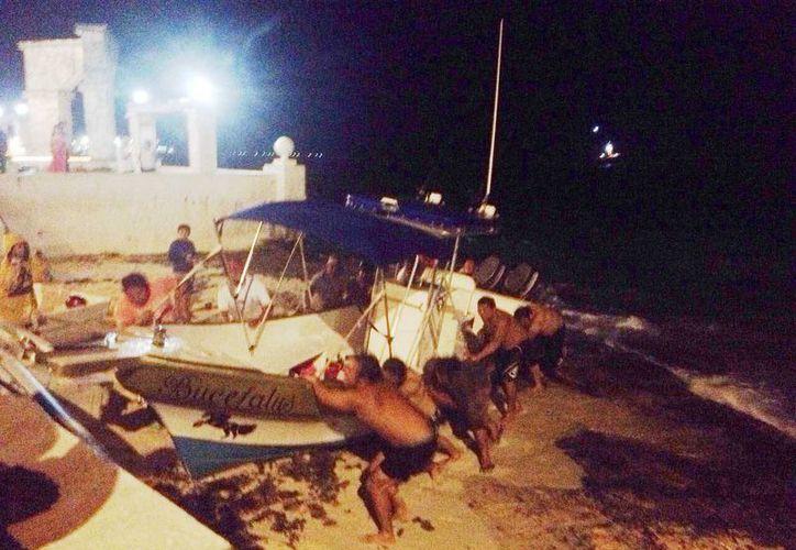 Varios ciudadanos ayudaron a dos trabajadores náuticos a rescatar una embarcación a punto de hundirse.  (Irving Canul/SIPSE)
