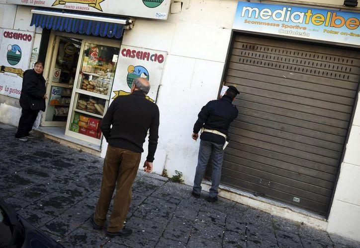 Un policía italiano asegura la tienda donde Pasquale Vigilia, el hijo de un jefe mafioso de la Camorra, fue asesinado por dos pistoleros, en Nápoles este martes 18 de diciembre. (EFE)
