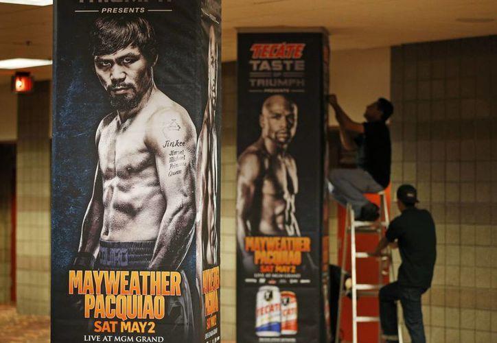 Empleados del MGM Grand Arena colocan posters alusivos a la pelea de box entre el invicto norteamericano Floyd Mayweather Jr y Manny Pacquiao, que se realizará este sábado en Las Vegas. (Foto: AP)