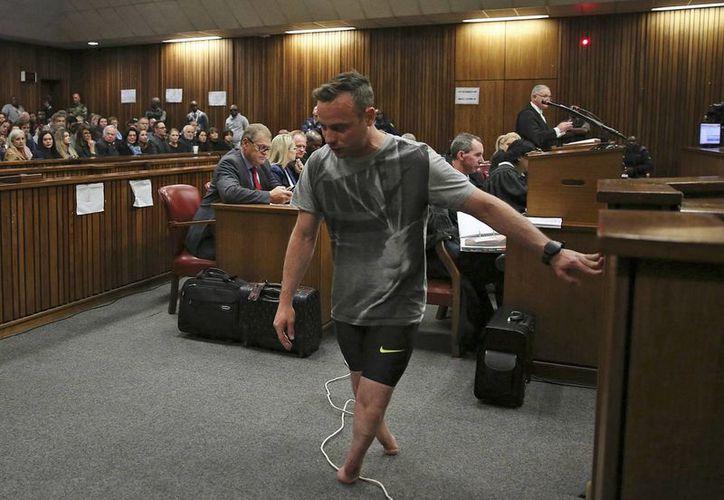 Las piernas prostéticas de Oscar Pistorius, en el suelo a la derecha mientras él camina sobre sus muñones para ilustrar un argumento de la defensa a favor de que se reduzca su sentencia durante una vista en el Tribunal Supremo, en Pretoria, Sudáfrica, el miércoles 15 de junio de 2016. (Siphiwe Sibeko, Pool Photo via AP)