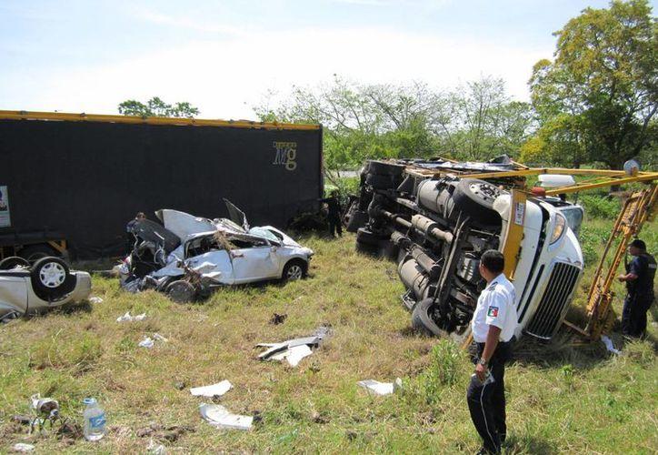Poco después de un accidente, un tráiler con doble semi-remolque con 12 automóviles a borda fue presa de la misma curva. (Edgardo Rodríguez/SIPSE)
