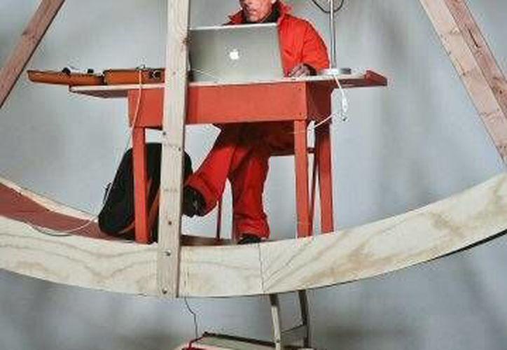 """Alex Schweder utiliza su computadora portátil durante el performance art """"In Orbit"""". (Agencias)"""