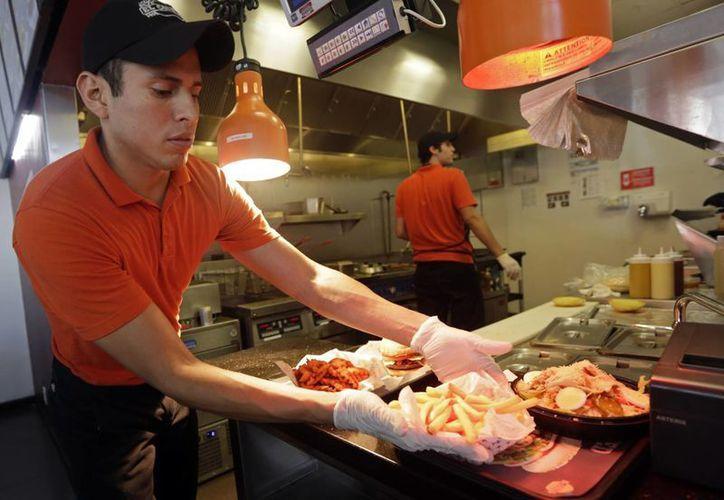 Un joven prepara un pedido en el restaurante de la cadena colombiana El Corral en Miami. (Agencias)