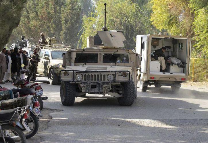 Oficiales de seguridad afganos toman posiciones durante un enfrentamiento armando entre las fuerzas de seguridad del estado y un grupo de extremistas en el Nuevo Banco de Kabul en Lashkar Gah, capital provincial de Hemland,  Afganistán. (EFE)