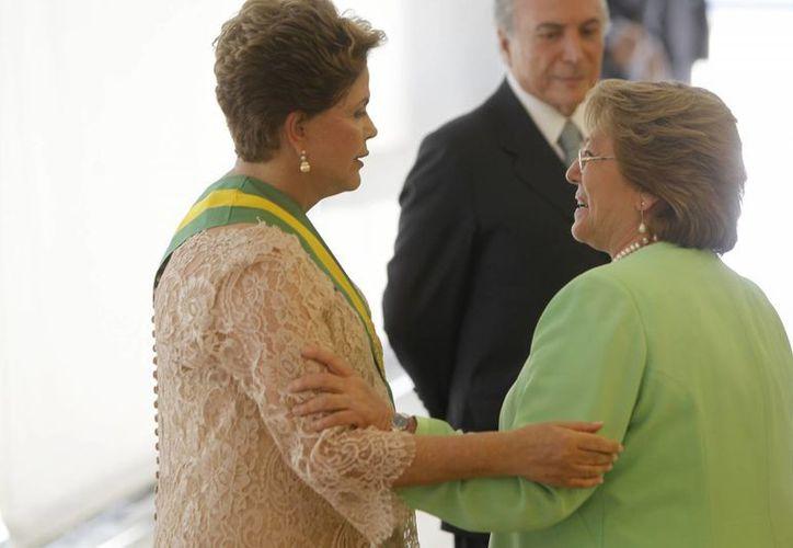 La presidenta brasileña, Dilma Rousseff (i), saluda a su homóloga de Chile, Michelle Bachelet, en la ceremonia de investidura en el Palacio de Planalto en Brasilia. (EFE)