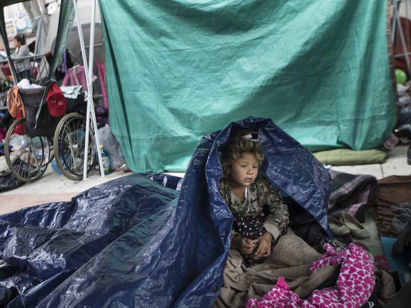 A girl who traveled with the annual caravan of Central American migrants awakens where the group set up camp to wait for access to request asylum in the U.S., outside the El Chaparral port of entry building at the US-Mexico border in Tijuana, Mexico. (AP)