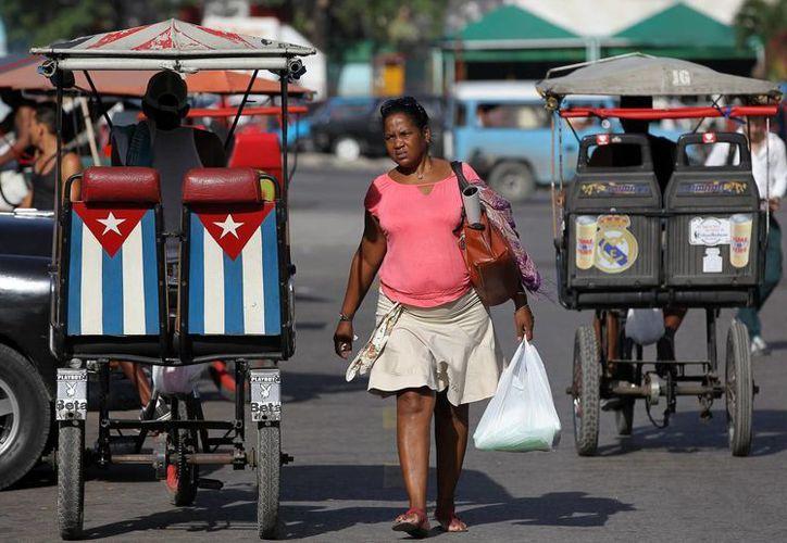 Una mujer camina junto a un bicitaxi adornado con una bandera cubana, en La Habana, Cuba, el pasado mes de junio. (Archivo/EFE)