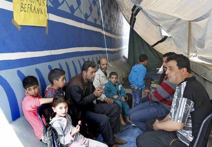 Una familia palestina procedente del campo de refugiados sirio de Al Yarmuk, en el sur de Damasco. (EFE)