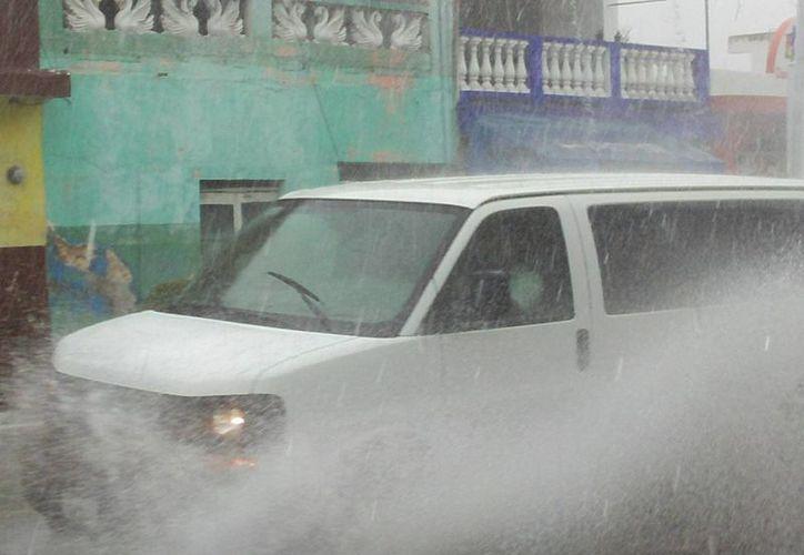 Una camioneta atraviesa a gran velocidad una encharcada calle del puerto de Progreso, Yucatán. (SIPSE)