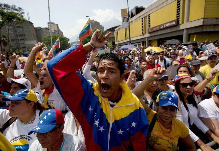 Estudiantes gritan consignas contra el presidente de Venezuela, Nicolás Maduro, durante la marcha del Día del Trabajo, ayer en Caracas, Venezuela. (Agencias)