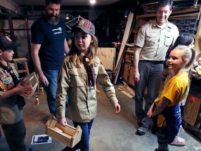 Tatum Weir, center, carries a tool box she built self. (AP)