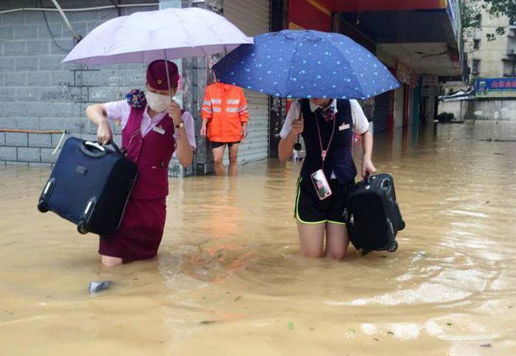 En Fuzhou, la capital de Fujian, la televisora estatal mostró imágenes de gente caminando con el agua hasta las rodillas en las principales vías de la ciudad. (Chinatopix vía AP)