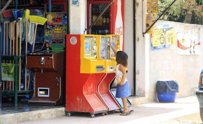 Una niña de cuatro años de edad intentaba meter una moneda en una de maquina. (Harold Alcocer/SIPSE)
