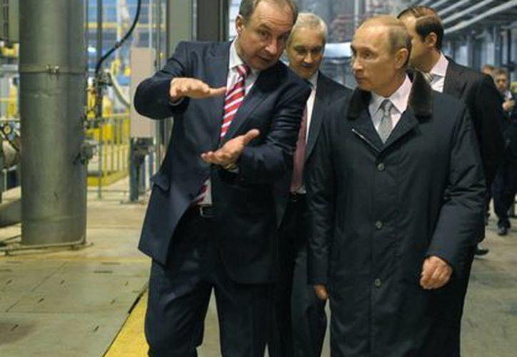 El presidente ruso Vladimir Putin (derecha) escucha la explicación de Valery Puchkov, jefe de una fábrica, duranye una visita a la ciudad de Petrosavodsk. (Agencias)