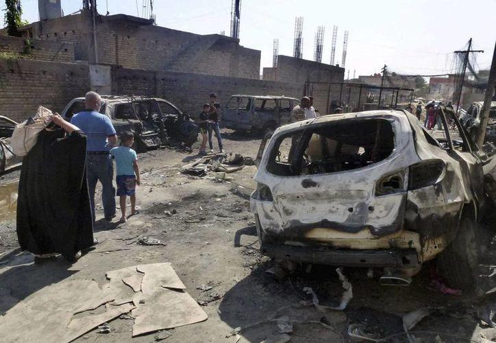 Unas personas pasan al lado de los restos de automóviles tras la explosión de un coche bomba en Bagdad.(Archivo/EFE)