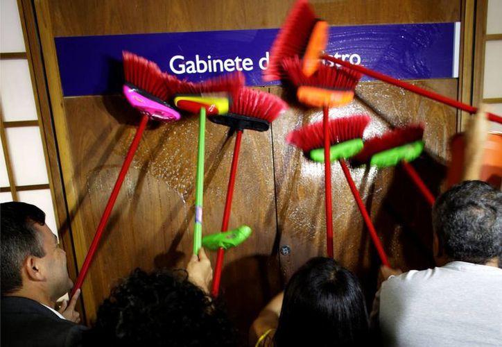 Personal talla escobas en la puerta del despacho del ministro de Transparencia, Fabiano Silveira, en demanda de que renuncie al cargo en Brasilia, el lunes 30 de mayo de 2016. El ministro renuncio. (AP Foto/Eraldo Peres)