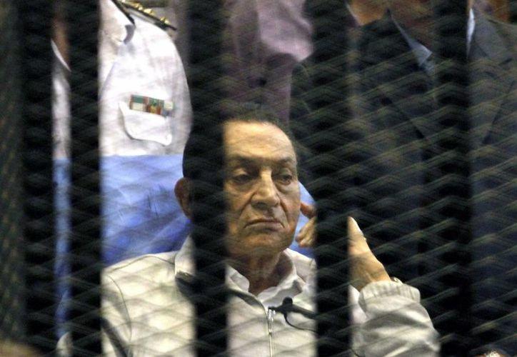 El expresidente egipcio Hosni Mubarak permanece sentado tras los barrotes durante una sesión celebrada en un tribunal en El Cairo, Egipto, hoy, lunes 15 de abril de 2013. (EFE)