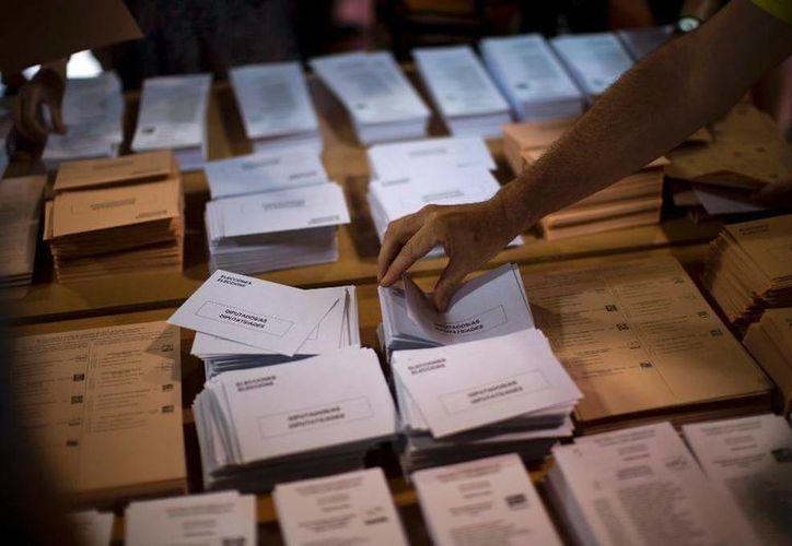 Un hombre escoge una papeleta antes de votar en las elecciones generales en Barcelona, España. (AP Foto/Emilio Morenatti)