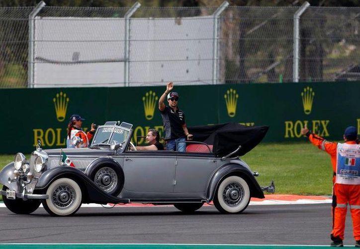 Sergio Pérez durante su llegada al Autódromo Hermanos Rodríguez, recinto que este domingo vivió el regreso de la Fórmula Uno a México después de 23 años. (AP)