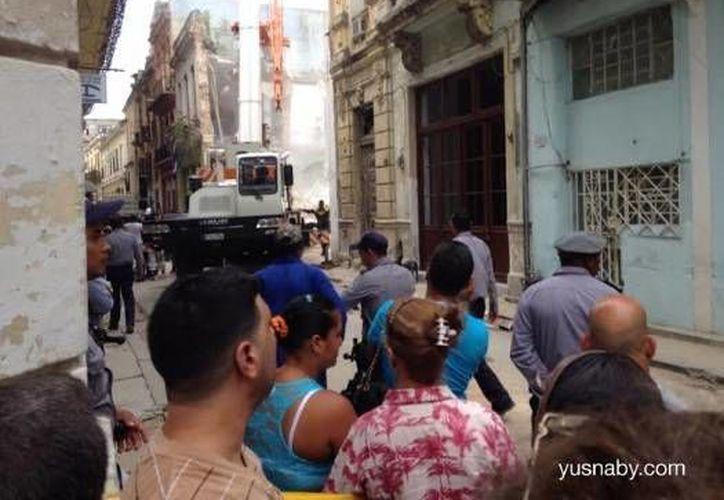 Vecinos observan la recogida de escombros del edificio que se vino abajo. (Foto de Yusnaby Pérez/Cubanet.org)