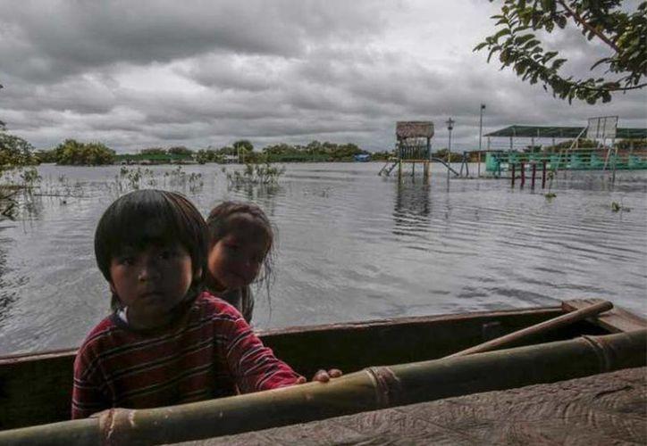 La familia Vásquez regresaba en un precario bote de madera a su comunidad en la selva. (Excelsior)