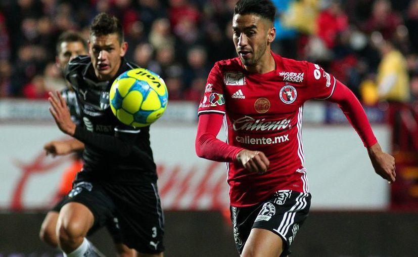 Juan Lucero (rojo)  conduce la pelota en al partido que su equipo, Xolos de Tijuana, derrotó a Rayados de Monterrey, en la jornada 8 del torneo Clausura de la Liga MX. (Jammedia)