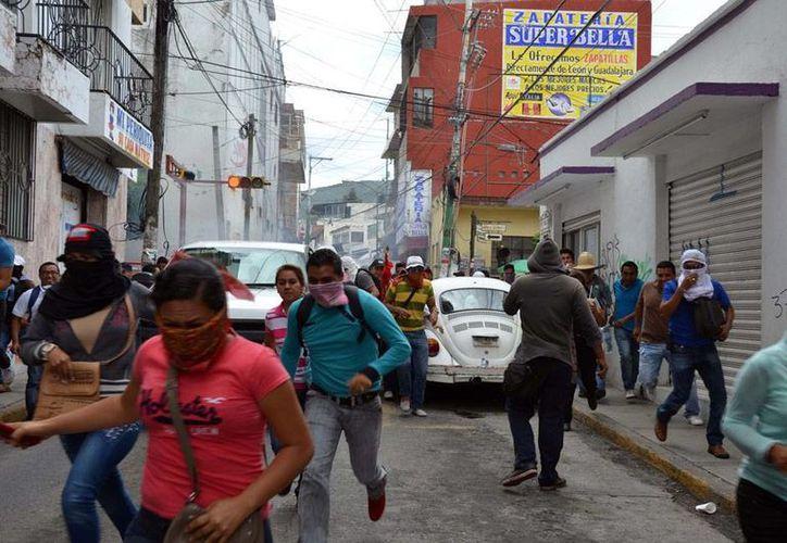 Maestros de la CNTE se retiraron de los plantones que mantenían en instalaciones de Pemex y el INE, en Oaxaca. La imagen no corresponde al hecho; son profesores de la CNTE de Guerrero que huyen tras el enfrentamiento con policías, en Chilpancingo. (The Associated Press)