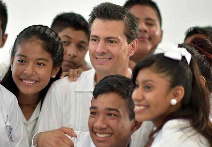 """El Presidente Enrique Peña Nieto dio inicio al Ciclo Escolar 2015-2016. En la imagen acompañado de los alumnos de la Escuela Secundaria Técnica Pesquera No. 15 """"José Vasconcelos Calderón"""" en Guerrero. (@PresidenciaMX)"""