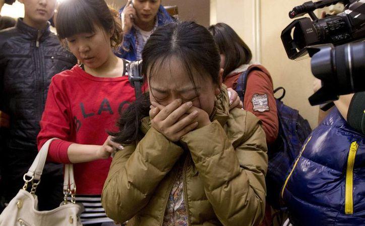 Un familiar de los desaparecidos permanece en el aeropuerto de Beijing a la espera de noticias sobre el vuelodel Being 777. (Agencias)