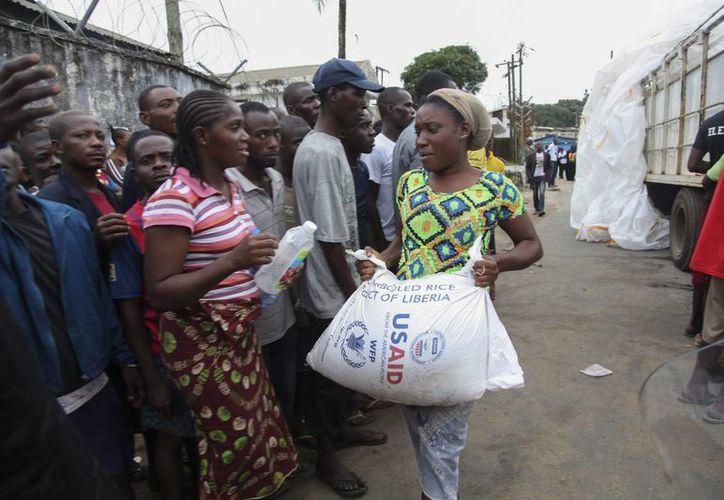 Varios vecinos liberianos de West Point reciben raciones de comida que distribuye el Gobierno como parte de su plan de cuarentena para la zona para ayudar a prevenir la expansión del mortífero virus del ébola en Monrovia, Liberia. (EFE)