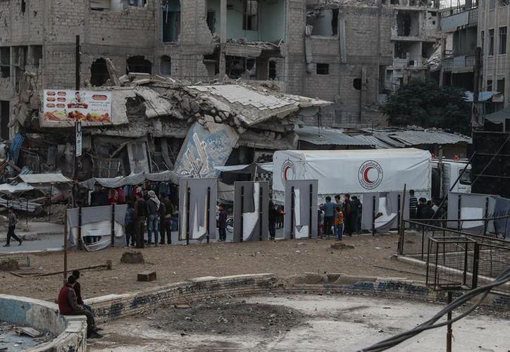 Personal de ayuda pasa por edificios destruidos en Douma, Siria.(Foto: EFE)