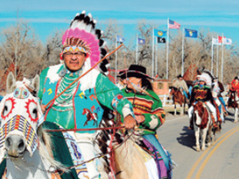 Darrin Old Coyote, then chairman of the Crow Tribe, leads riders past Veterans Park as Crow Tribe members gather for the inaugural parade in Crow Agency, Mont. (AP)