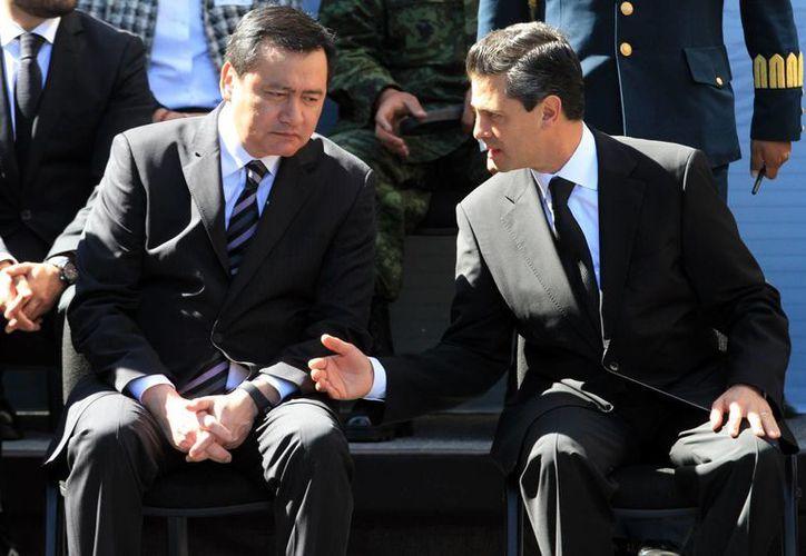 El presidente Enrique Peña Nieto (d) con el titular de la Segob, Miguel Osorio Chong, ayer en la entrega de reconocimientos a personal de Pemex. (Notimex)