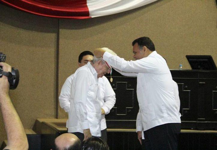 Imagen del momento en que el gobernador Rolando Zapata le pone la medalla al maestro Roldán Peniche Barrera. (SIPSE.com)