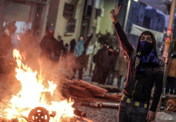 Un manifestante desafía a las autoridades en el marco del funeral de un menor que murió a consecuencia de un golpe con una granada de policía. (Agencias)